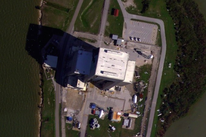 An aerial reconnaissance plane surveyed damage from Hurricane Matthew along the U.S. East Coast, revealing exterior siding stripped from SpaceX's payload processing facility at Cape Canaveral. Credit: NOAA