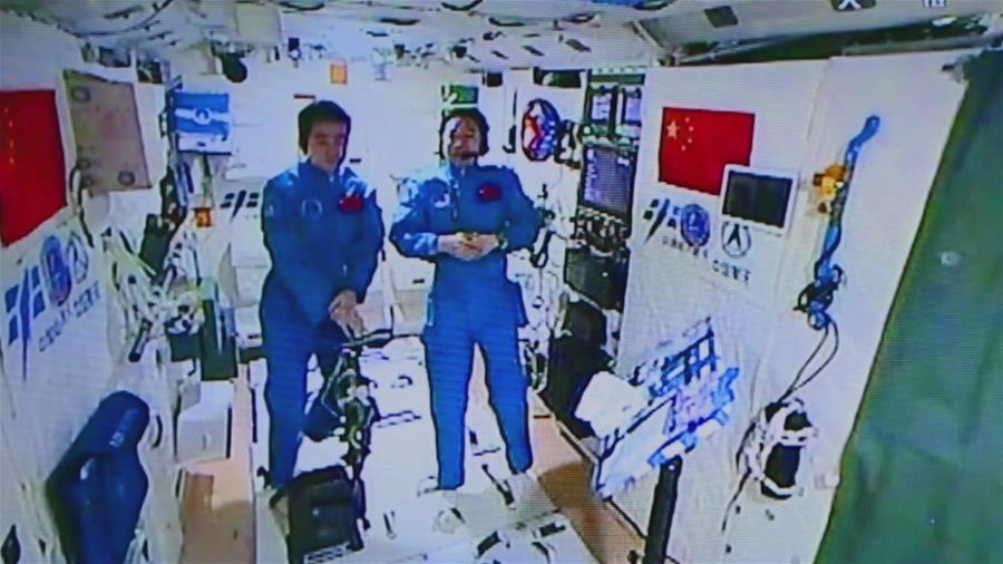 Chinese astronauts Chen Dong (left) and Jing Haipeng (right) conducted an interview with China's state-run Xinhua news agency Tuesday from inside the Tiangong 2 space lab. Credit: Xinhua