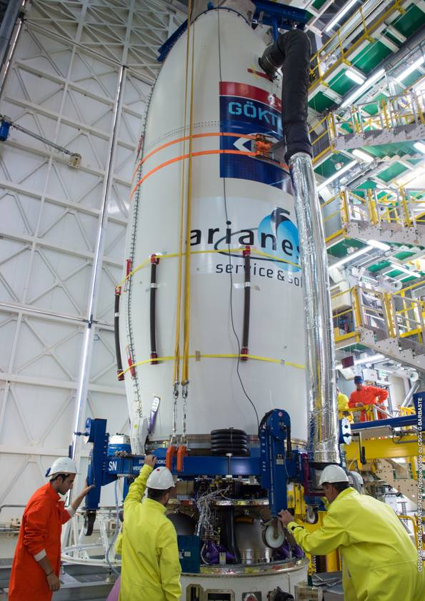 Ground crew members lower the Gokturk 1 satellite inside its payload fairing on top of the Vega rocket's fourth stage. Credit: ESA/CNES/Arianespace – Photo Optique Video du CSG – G. Barbaste
